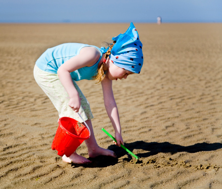 Girl At Beach With Bucket And Rake Stock Photo - Download Image Now