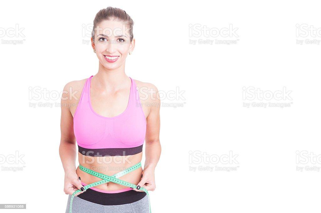 Girl at gym holding centimeter around waist stock photo