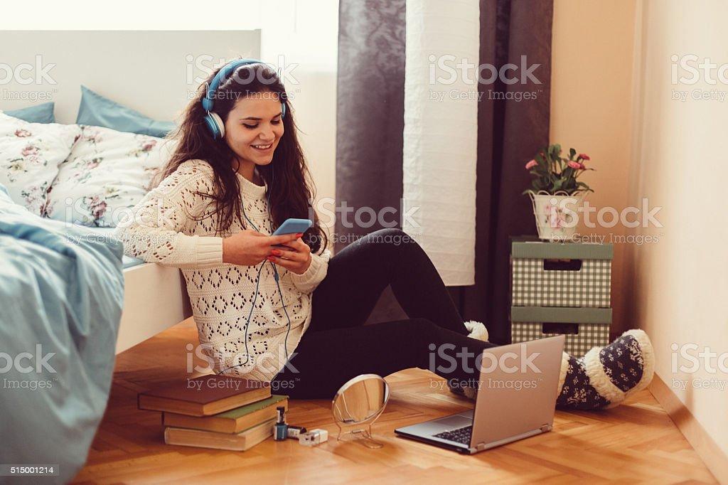 Chica en casa mensajes de texto en teléfono inteligente - foto de stock