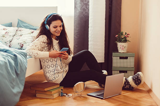 Girl at home text messaging on smartphone Happy girl sitting on the floor and listening to the music girl bedroom stock pictures, royalty-free photos & images