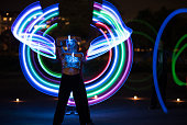 Colorful light painting at night with female model standing in front.