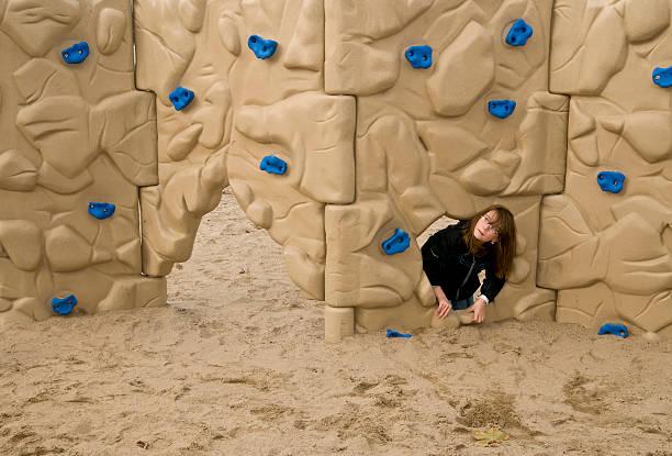 Girl at sandbox climbing wall stock photo