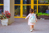 Curly cute little toddler girl back to school with holographic schoolbag or satchel, child going to kindergarten. Toddler kid first day at school or preschool.