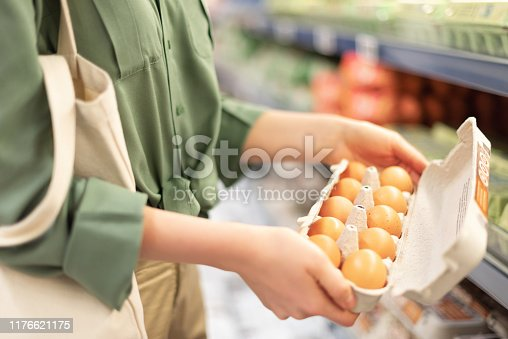 Girl at supermarket holding cotton shopper bag and buying eggs in craft package without plastic bags. Zero waste, plastic free concept. Sustainable lifestyle. Banner