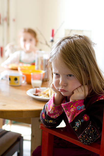 girl at table, doesn't want to eat stock photo
