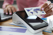 istock Girl at table holds credit card over bank terminal 1220141522