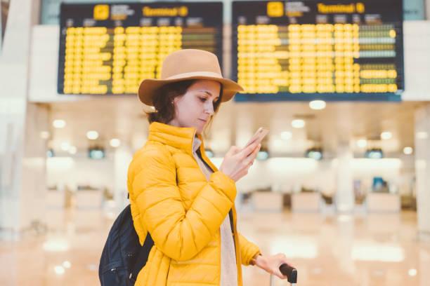 gadis di bandara memeriksa papan keberangkatan kedatangan - traveler new york potret stok, foto, & gambar bebas royalti