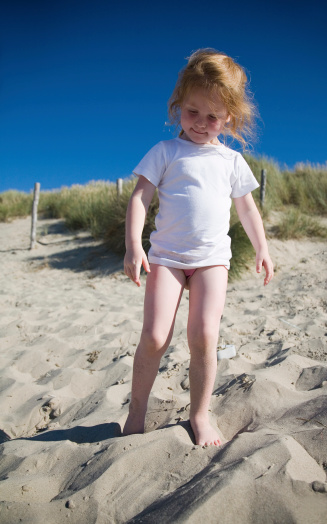 Girl At The Beach In Search Of Hidden Treasures Stock Photo - Download Image Now
