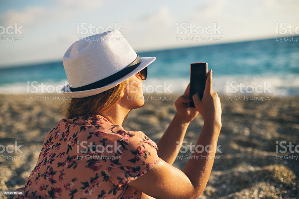 Girl at the beach texting on smartphone stock photo