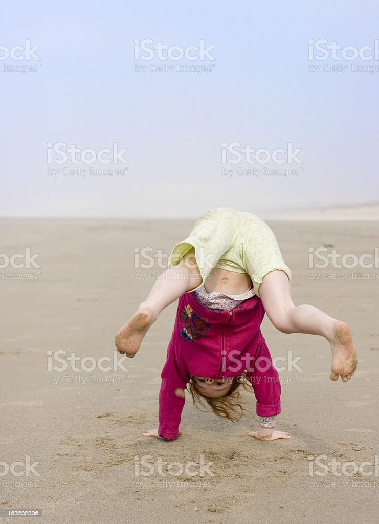 girl at the beach, trying to do a hand stand royalty-free stock photo