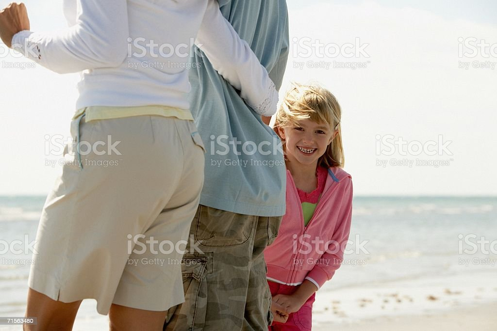 Girl at the beach with parents royalty-free stock photo