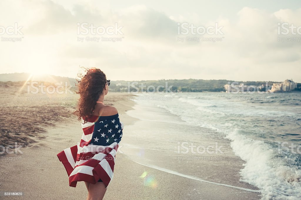 Girl at the beach wrapped in the usa flag stock photo