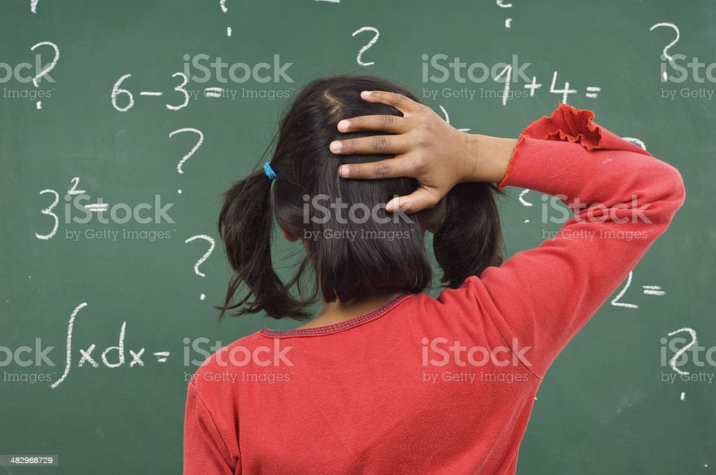 girl at the blackboard little girl in a red t-shirt in front of a green blackboard with mathematic formulas African Ethnicity Stock Photo
