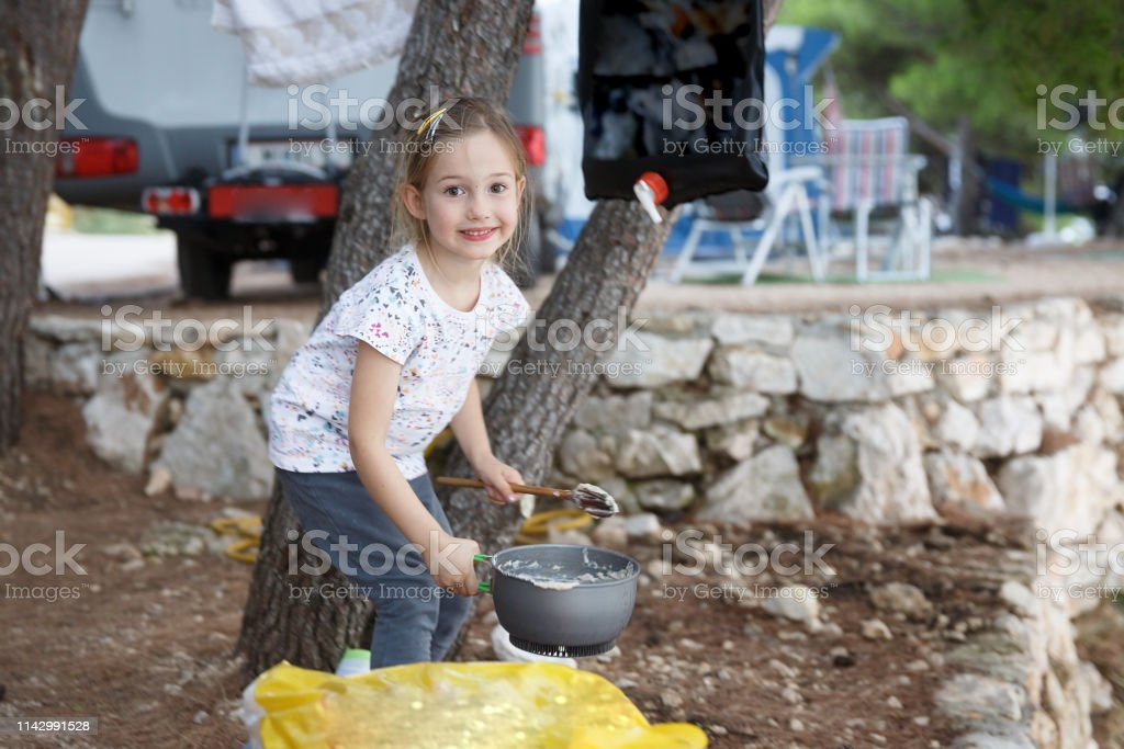 Girl at the campsite, cooking food in outdoor kitchen. Active natural...