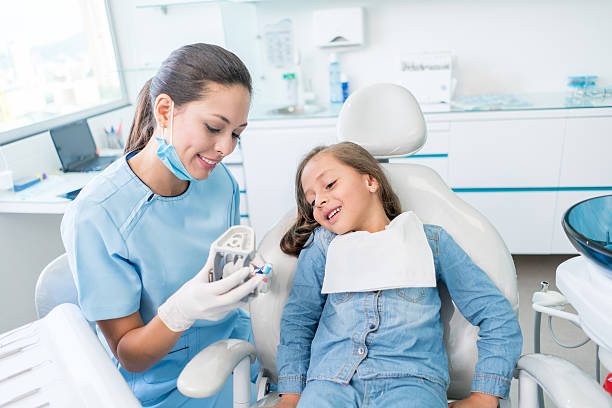 girl at the dentist learning how to brush her teeth - kieferorthopäde stock-fotos und bilder