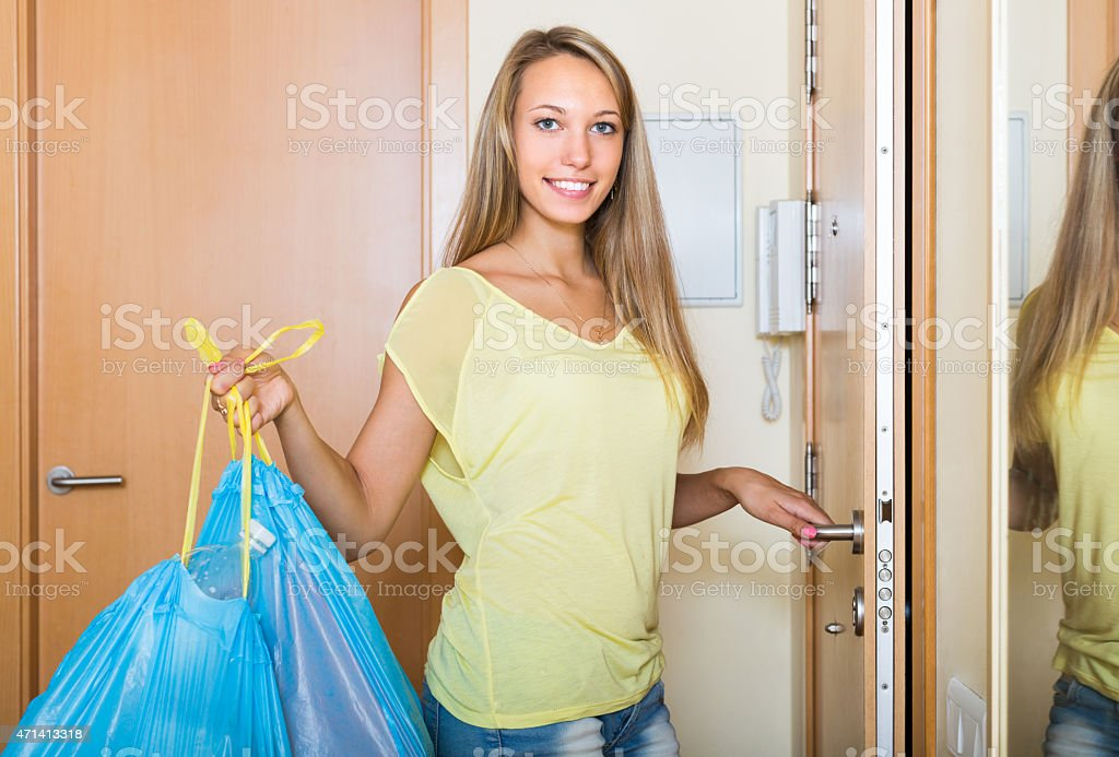 Girl at the door with trash bags stock photo
