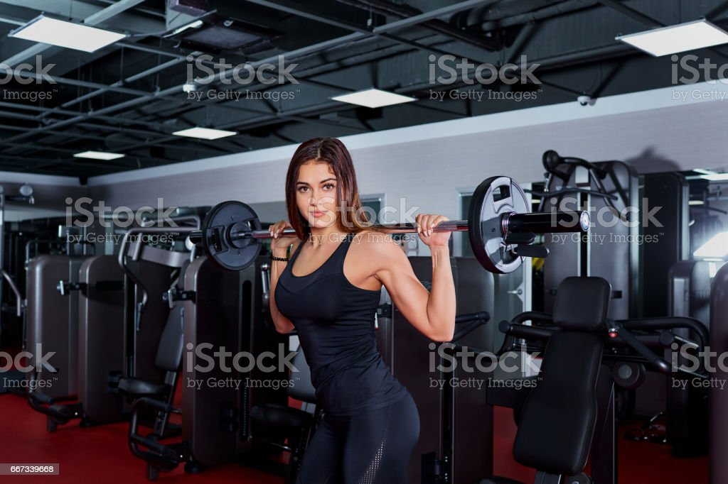 Girl athlete doing exercises with a barbell. Sport Club. stock photo