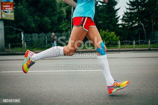 Omsk, Russia -  September 20, 2015: girl athlete running a marathon, knees in blue kinesiology taping during Siberian international marathon