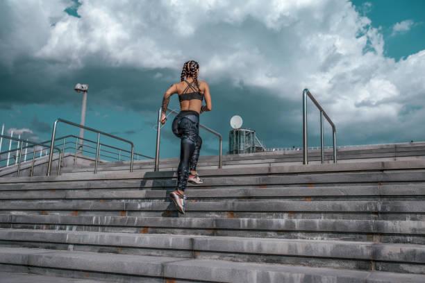 mädchen-athlet, sommer-stadt. musikhören mit kopfhörer, springt morgens joggen auf der treppe. in leggins turnschuhen. frau mit tattoos. in händen eines smartphones. freiraum für text. - tattoo ideen stock-fotos und bilder