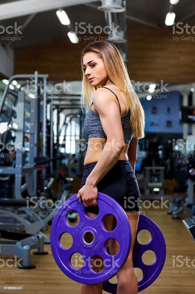 Girl athlete with a barbell in the hands of the gym stock photo