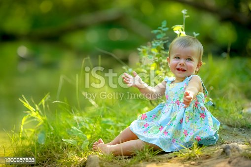 487217358 istock photo Girl baby one barefoot near water in the forest 1200657833