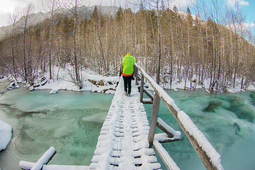 Girl backpacker walking on a bridge over a frozen turquoise ice river in the winter forest in the mountains