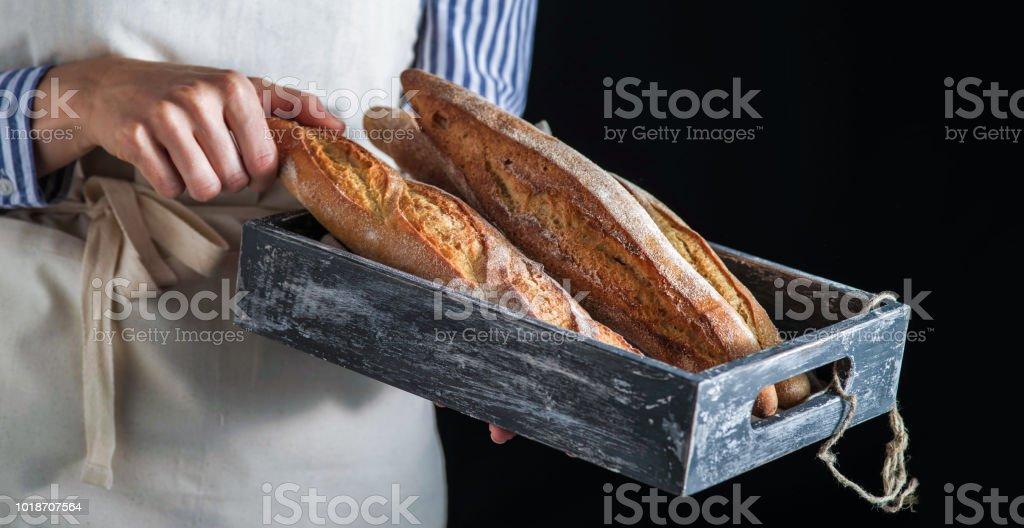 Girl baker holding freshly baked baguettes. стоковое фото