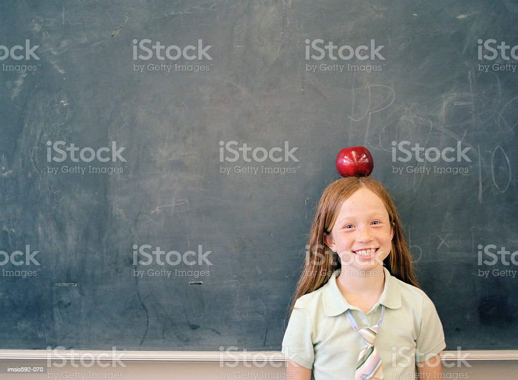 Girl balancing an apple on her head royalty free stockfoto