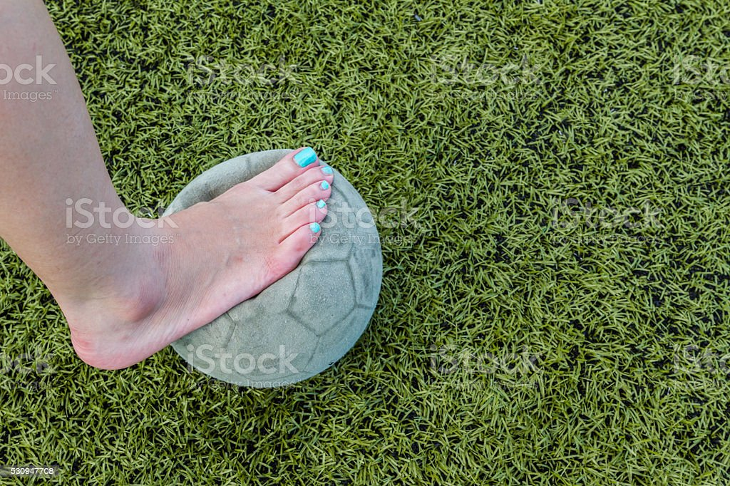 Girl Barefoot and old soccer ball stock photo