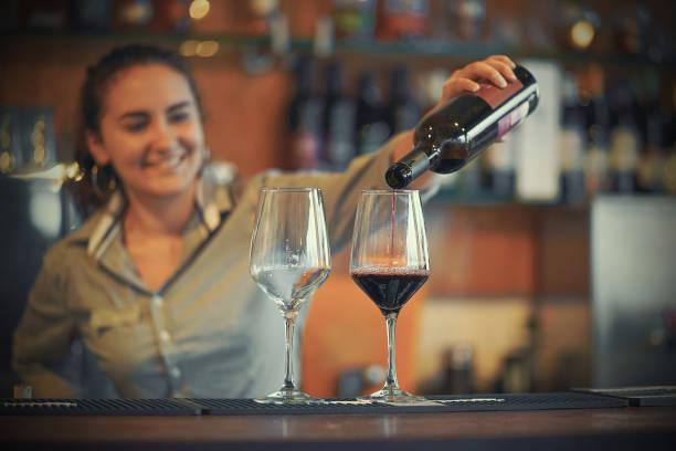 Mädchen Barkeeper gießt Rotwein in zwei Weinglas – Foto