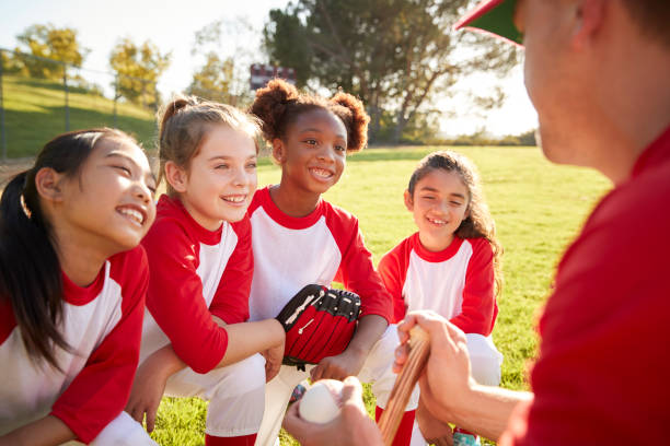 Girl baseball team in a team huddle with coach, listening Girl baseball team in a team huddle with coach, listening baseball sport stock pictures, royalty-free photos & images