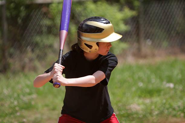 Girl batting in softball stock photo