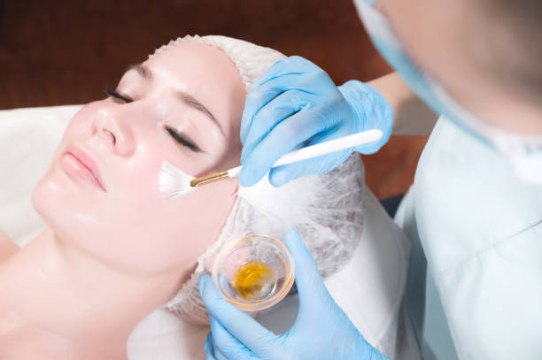 Girl beautician applies a brush to rejuvenate a mask on the face of an attractive girl in a spa salon. stock photo