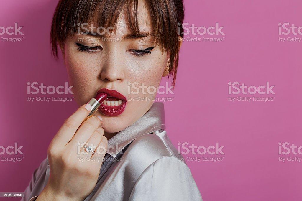 Retrato de menina beleza colocando batom vermelho em enquanto olhando para baixo - foto de acervo