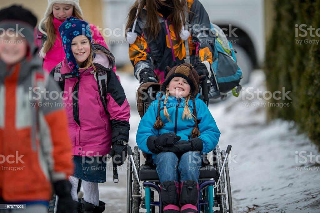 Niña llevando a cabo en una silla de ruedas - foto de stock