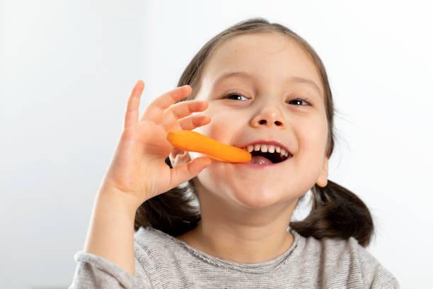 Mädchen beißen Karotte. – Foto