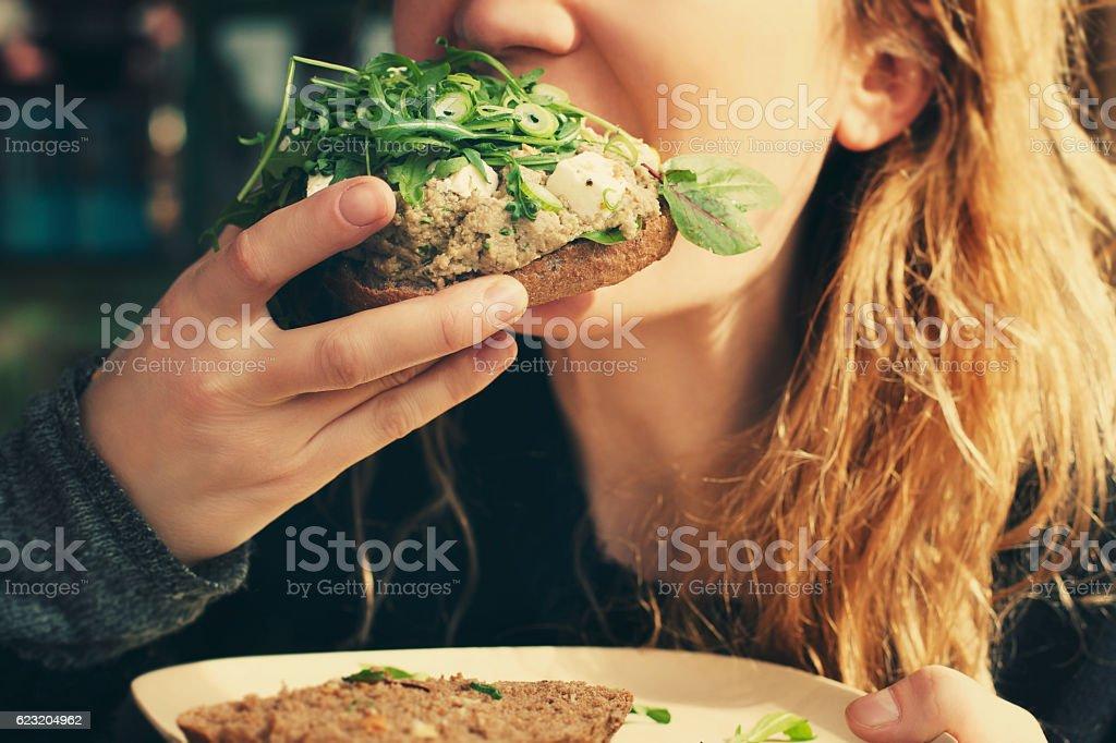 Girl biting veggie sandwich. stock photo
