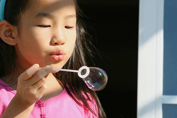 girl blow bubble stock photo