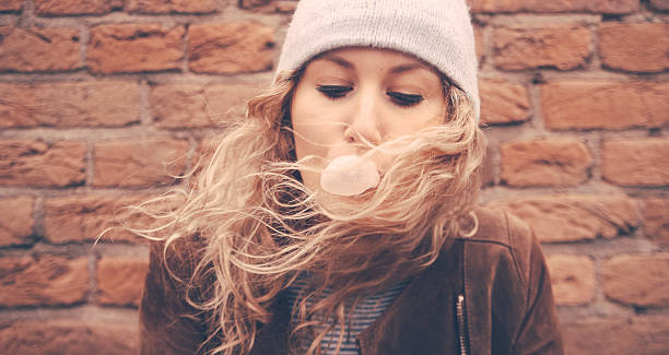 Girl blowing bubble gum with a brick wall behind her stock photo