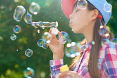 Side view of lovely girl in casual outfit blowing bubbles while spending time in park on sunny day after school