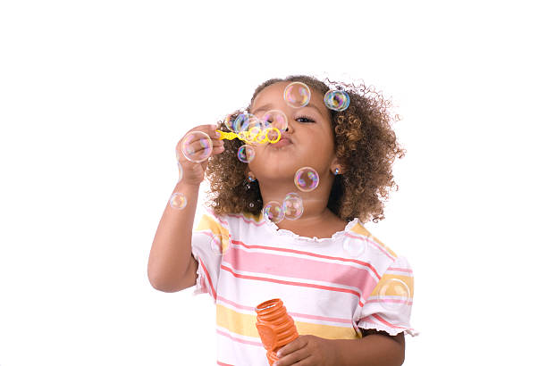 Girl Blowing Bubbles on White Background stock photo