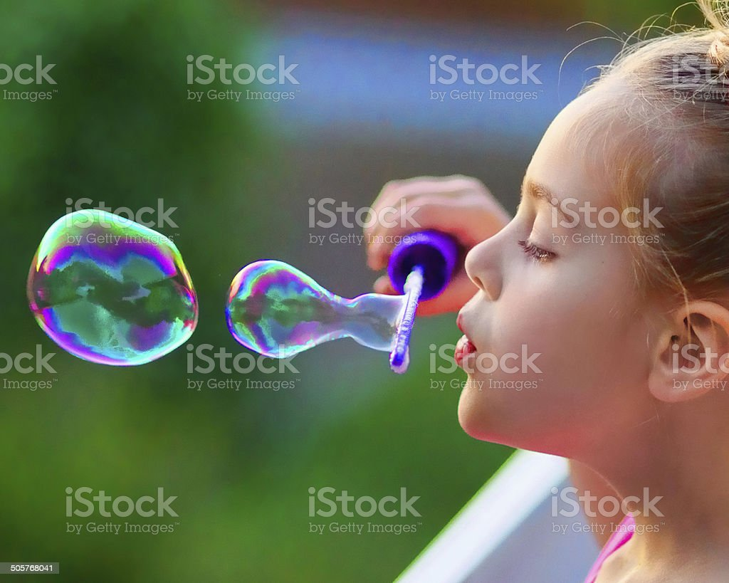 Girl Blowing Bubbles stock photo