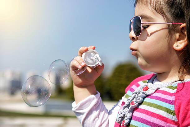 mädchen blasen blasen  - sonnenbrille kleinkind stock-fotos und bilder