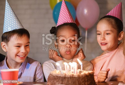 istock Girl blowing candles on birthday cake, celebrating birthday 1092674554