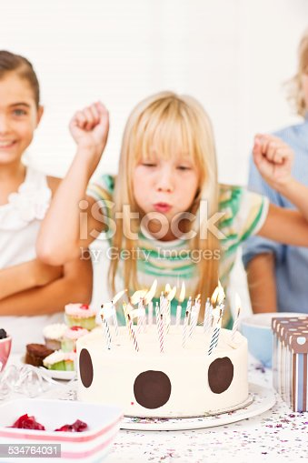 istock Girl blowing off the candles on her birthday cake 534764031