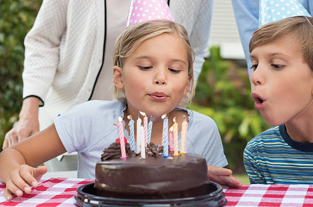 Girl blowing out the candles Young girl blowing out birthday candles of chocolate cake. Portrait of young girl celebrating birthday with family and brother. Brother helping sister blow candles on birthday cake. birthday wishes for daughter stock pictures, royalty-free photos & images