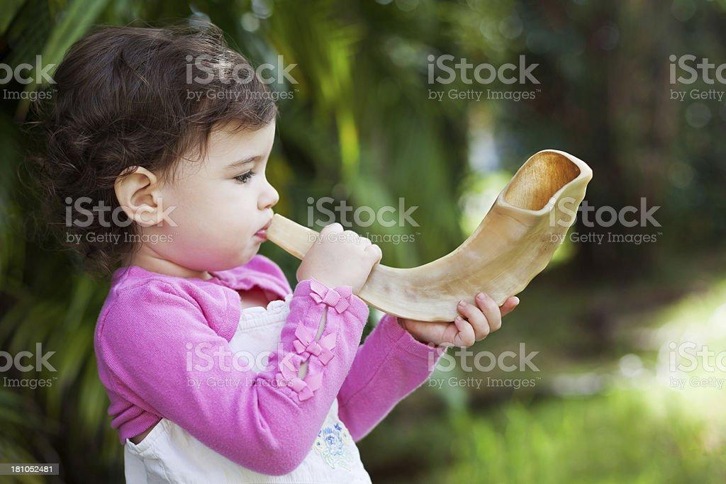 Girl blowing shofar stock photo