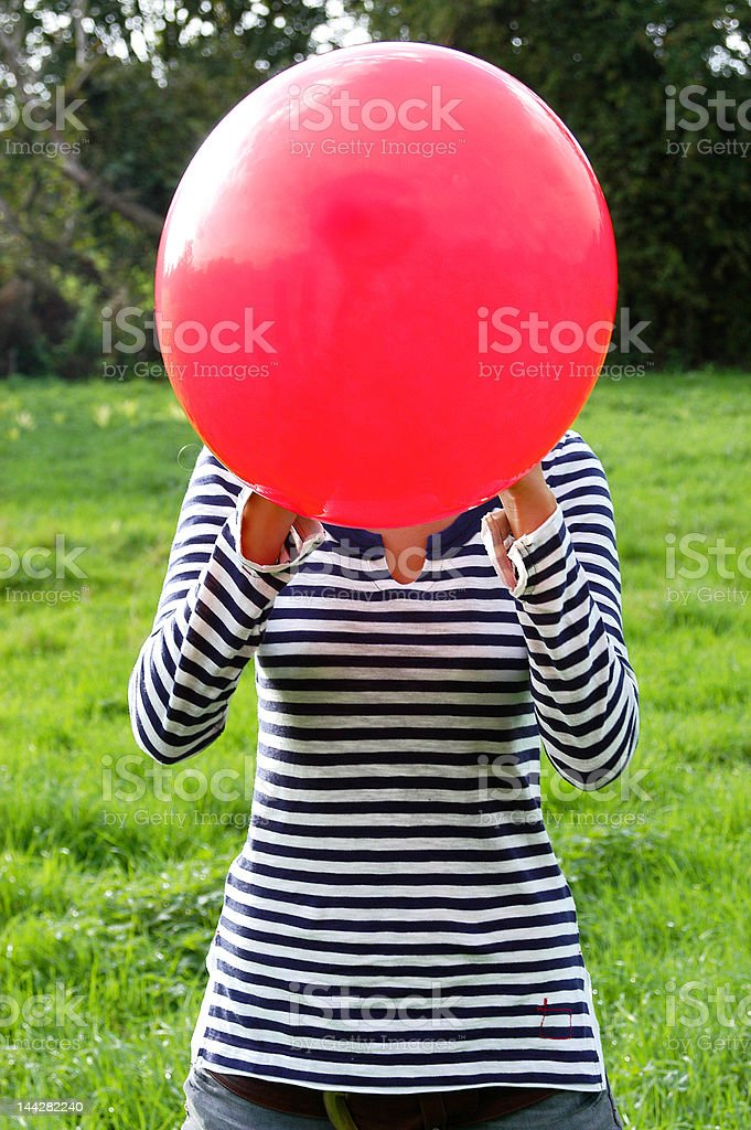 Girl blowing up red balloon royalty-free stock photo