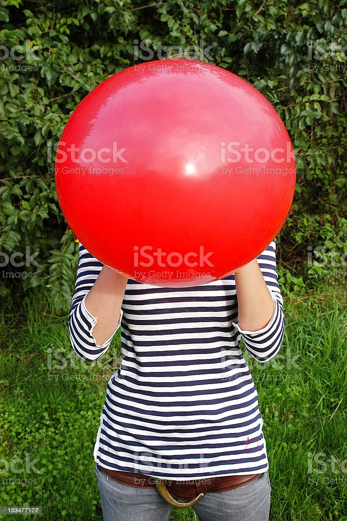 Girl blownig up red balloon royalty-free stock photo