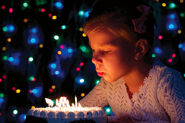 girl blows out the candles on the cake stock photo